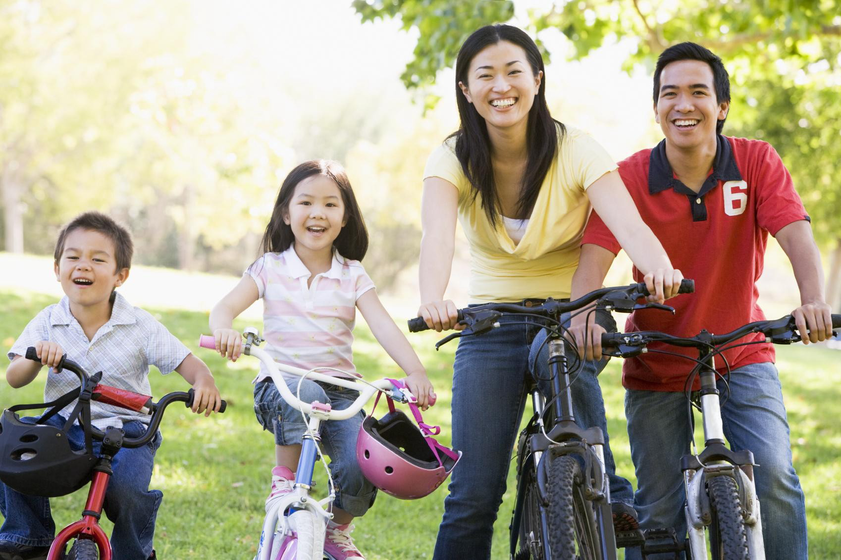 Family on bikes outdoors , smiling because they have healthcare services